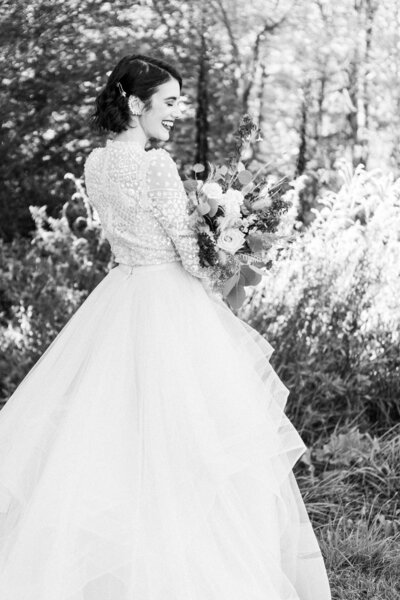 Bride laughing in black and white image holding wild whimsical floral bouquet.
