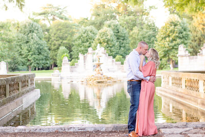 Summer Sunset Engagement Session with pink maxi dress couple kissing  by water  at The Ruins  in Tower Grove Park in St. Louis by Amy Britton Photography Photographer in St. Louis