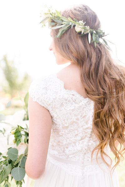 Bride in Orange County, CA. Modest lace wedding dress. Greenery and floral crown on her head.