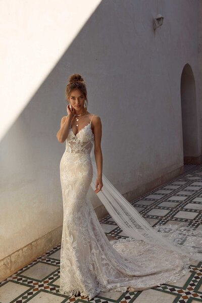 A gown made for a feast under the Tuscan sun or a long lunch down a dazzling sandy beach – Anya is adaptable and perfectly sophisticated to meet any bride's vision. Her botanically beaded lace adds texture and depth as the mocha undertones (shown) enhance her exquisiteness. Anya's feminine fishtail silhouette looks dreamy on curves and falls into a small train behind her. The barely-visible spaghetti straps move into a lovely curved low- back which is soft and flattering on her brides.  Anya has the incredible ability to adapt to her surrounds and doing so with a detachable train included with the gown. Joining just at the dip of the curved back is where a sweet tulle bow forms before cascading into embroidered lace fanning behind. It's the loveliest addition to add to her bride's ceremony before detaching it for her reception, so she can relax into the evening.