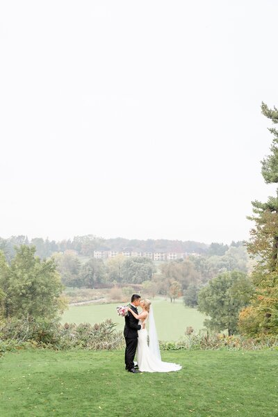 Newlywed couple kissing on a hill at Lionhead Golf Club