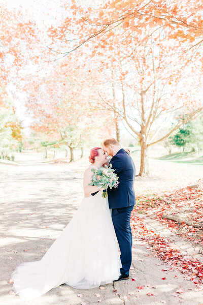 Bride and groom pose with colorful fall trees.