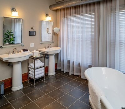 Quinnimont's tiled bathroom has two sinks, shower and bathtub.
