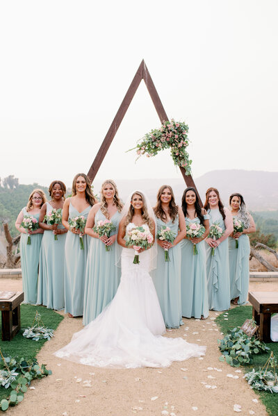 dusty blue bridesmaid dresses in front of triangle ceremony arch