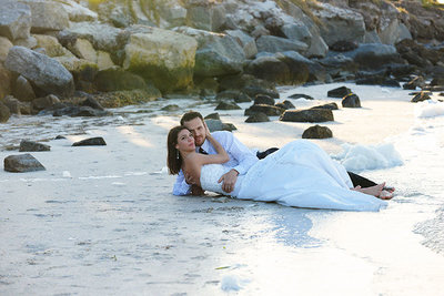 Bride and Groom laying in the sand on waters edge at Fred Howard Park Beach