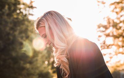 blond woman with sun behind her