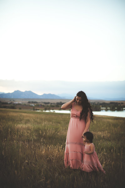 Mother-dances-in-field-with-daughter-at-sunset