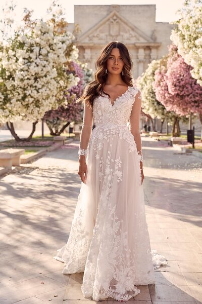 The epitome of garden weddings, Meadow is the show stopping elegance every bride wants to live out. Her lush and grandeur skirt, embellished with botanical embroidery has a very Italian couture elegance about her. Her 3D floral lace has been expertly placed to cascade from detailed clusters around her neckline, to blossoms across the thin overlay before flourishing down the full bodied gown. Meadow is a mirage of glamour designed to showcase her feminine grace with a touch of dramatic sophistication which is mirrored when she walks away. As she turns, a key-hole cut out exposes her back, as translucent lace mixed with flower appliqués climb and meld into her bodice. While she may look sweet, with her sheer long sleeves and elusive buds, she has an unexpected lust revealed in her V-neckline. Meadow is by no means a traditional ball-gown, instead she maintains a soft, full-flowing skirt that sweeps behind into a statement making train – adding just enough drama to a provincial ceremony or alfresco reception.