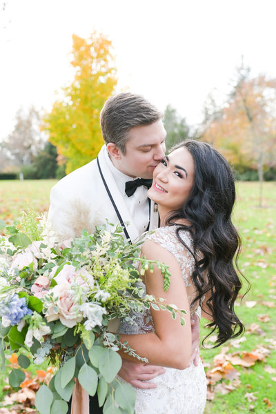 Groom kisses bride's cheek at Inn at Fernbrook Farms wedding