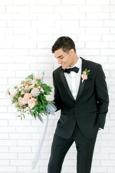 Groom posing with his bride's bouquet