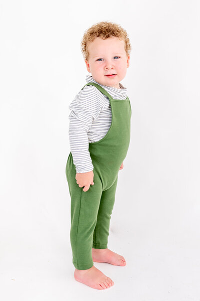 A toddler wearing a knit green romper