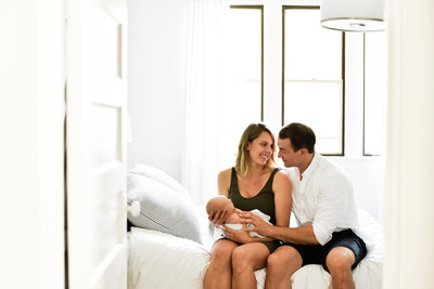 Family photo with newborn in a white bedroom
