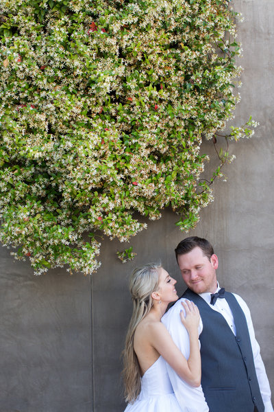 Couple next to flowers at their wedding before going to the Immaculata