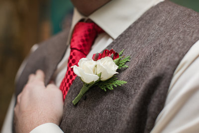 groom with a winter boutonniere at the Golden Horseshoe Inn wedding venue
