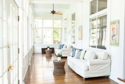 Living space with big windows around, laminate wood floors, and a coastal vibe