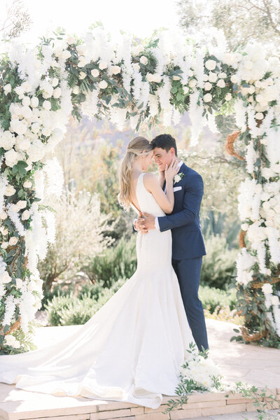 bride and groom in navy suit under white floral arch