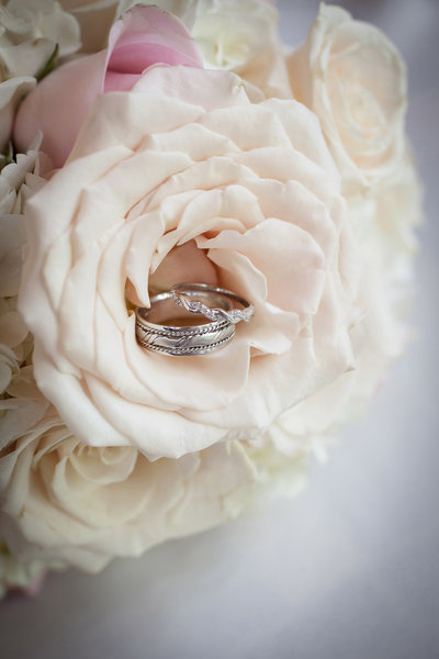 Silver edding bands inside a soft pink rose