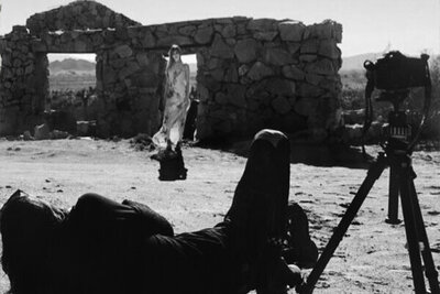 BTS black and white Mark Maryanovich photographing female musician Kendall Rucks standing in front of stone building in desert wearing long dress tripod beside him