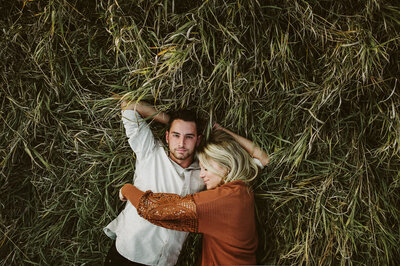 Couple laying in the tall grass with green and orange