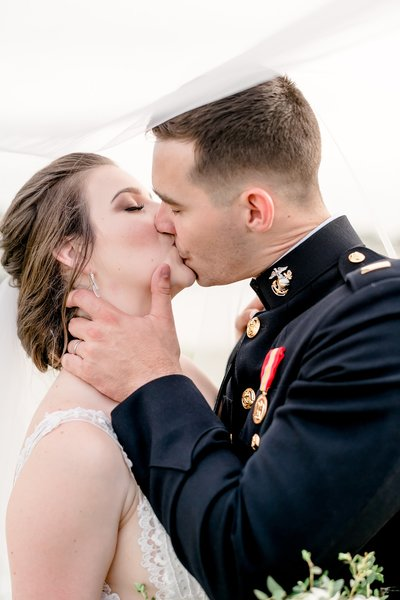 military bride and groom kissing under veil by dallas wedding photographer catie ann photography