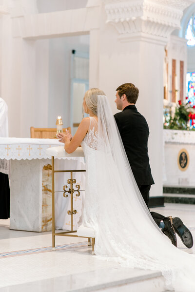 bride and groom kneel at the altar