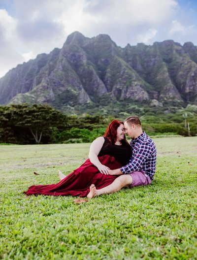 Couples Photography Oahu Hawaii,  couple sitting in the grass together by a mountain