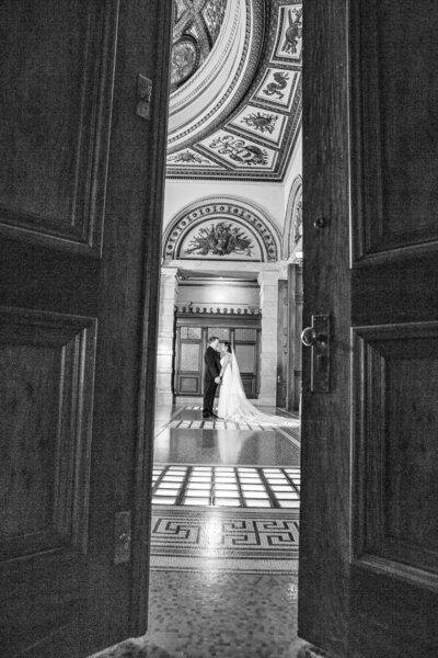 An open door show a bride  and groom  in a classy architecture.