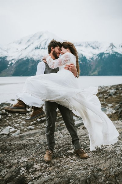windswept bride and groom at bird point with mountain and ocean back drop after their Alaska elopement