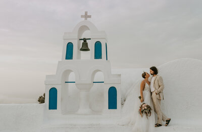 Bride and groom in front of santorini church in Oia