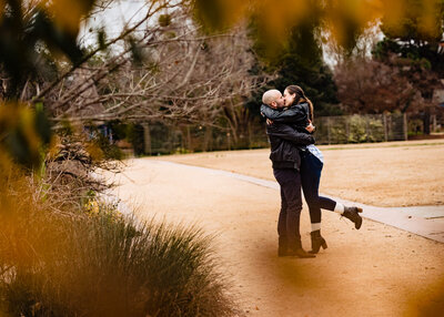 Woman kisses her fiance at JC Raulston Arboretum during a Raleigh engagement session