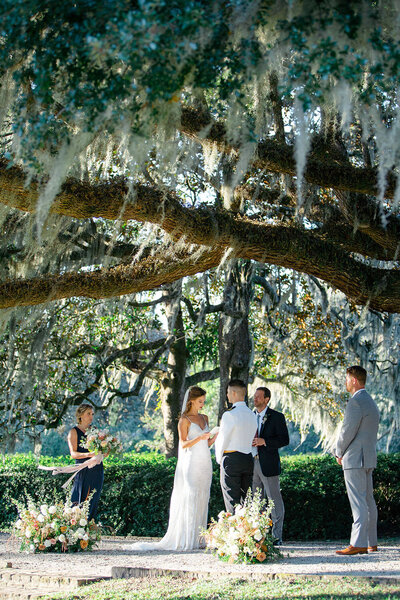 Live oak with Spanish moss wedding ceremony with dramatic ground floral arrangements flanking the couple