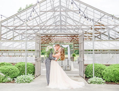 Glass atrium wedding venue photo of bride and groom kissing