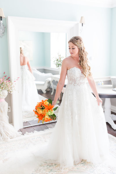 Beautiful bride poses in her wedding gown while holding orange and yellow bouquet