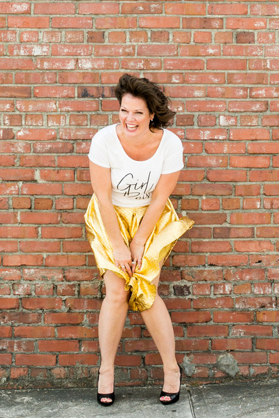 Female business owner laughs and poses for photo in front of a brick wall