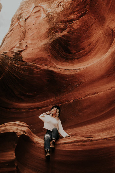 woman smiling while sitting on red rock