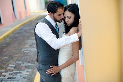 a bride and groom lean against a colorful wall in puerto rico