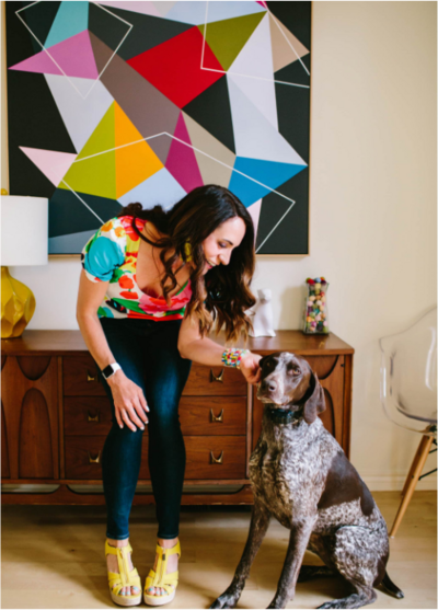 Woman in a bright colorful home with a dog