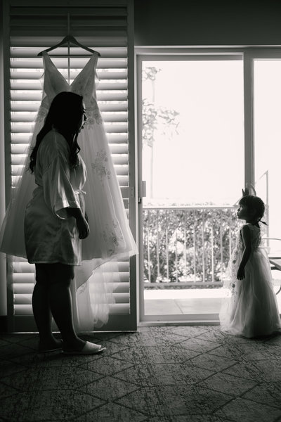 Black and white image of a bride and flower girl standing in front a window