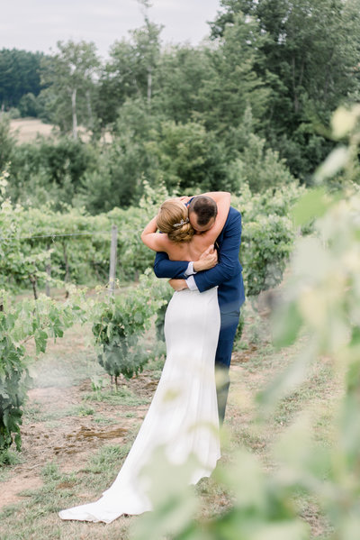 Bride and groom hug at Pleasant Hill Vineyard Wedding in Hart, MI photo by Grand Rapids wedding photographer Cynthia Boyle
