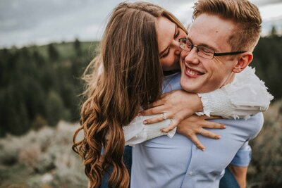 girl on back of boy kissing on a mountain in tennessee engagement photos