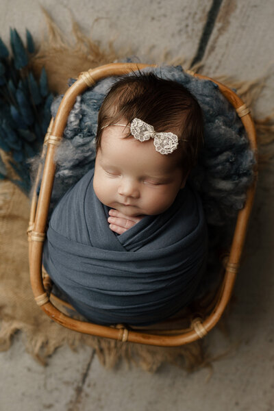 newborn baby girl wrapped in blue in a basket