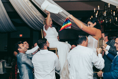 brides lifted up during horah at rusty pelican