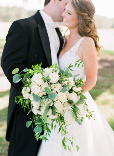 Bride with White and Ivory Floral and Greenery Bouquet with Groom in Black Tuxedo