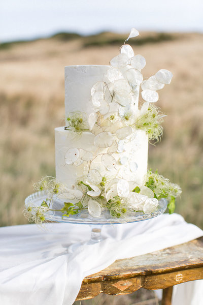 Wedding cake with lunaria on a table in the English countryside