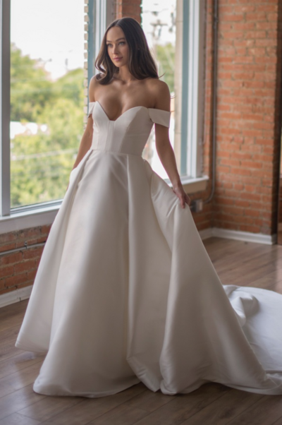 The Boady gown features a timeless yet modern silhouette with detachable sleeves and an exaggerated train in our new Majesty Mikado. The dramatic bodice seaming, and draped sleeve detail add visual interest while still being easy to wear for a modern classic bridal moment.