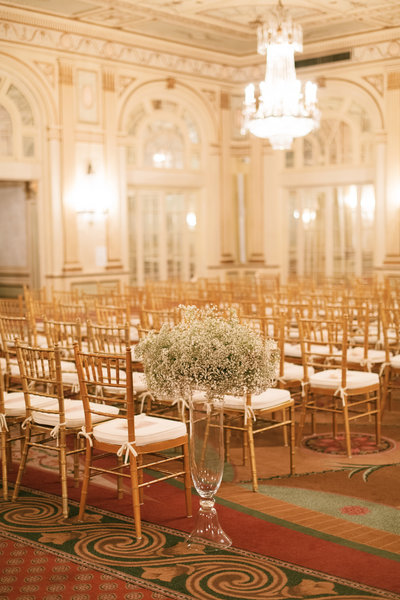 chiavari chairs for the ceremony at the brown hotel with tall baby breath centerpieces in glass vases