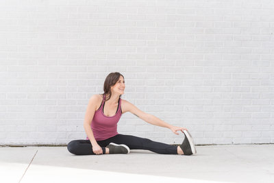 Fitness instructor stretches and smiles in front of white brick wall during branding photography session