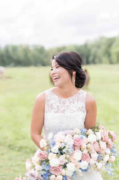 Beautiful Asian bride with big bouquet smiles in a field