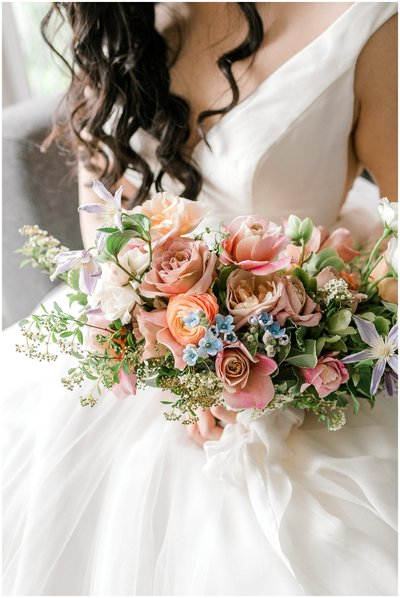 bride holds her colorful spring bouquet filled with garden roses, ranunculus, clematis, tweedia, and spirea.