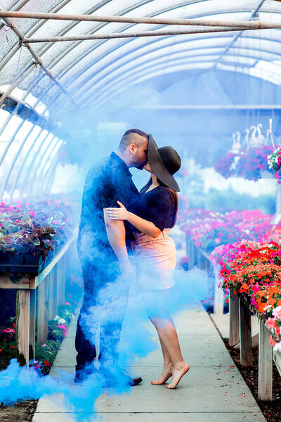 man-and-woman-kiss-blue-smoke-greenhouse